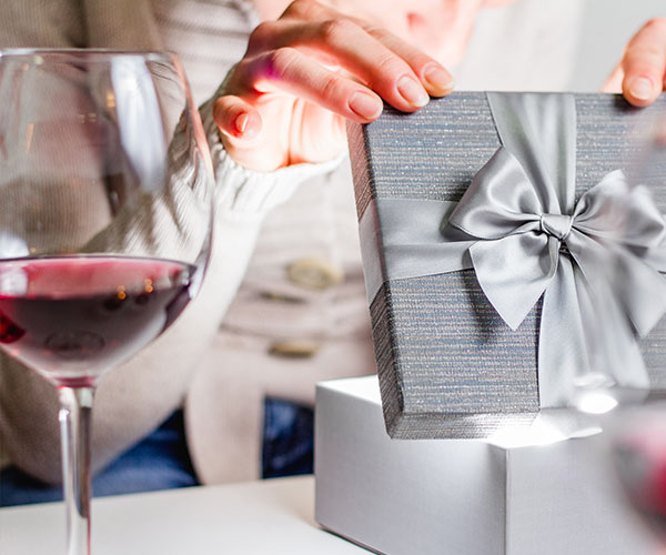 woman opening a gift with wine glass