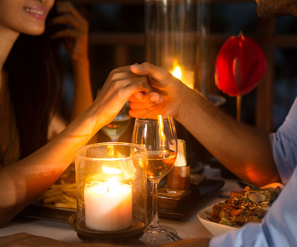 holding hands over candle light dinner